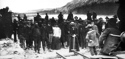 Ceremony of driving the last spike at Whitehorse, June 8, 1900. Bill Robinson is the man with the white forehead, facing the camera. On his left is an engineer named Hislop, and next to him M.J. Heney.