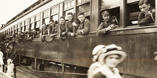 Canadian soldiers in Ontario lean out of a rail car as they depart for the coast circa 1915–1916. Soon, they will be boarding troop ships bound for England.