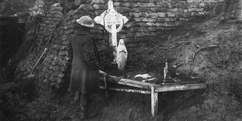 A Canadian takes a moment at the graveside of a Canadian who was killed in 2nd Battle of Ypres. November, 1917. Photo: Dept. of National Defence/LAC, MIKAN no. 3403359.