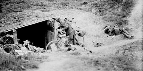 A Canadian cyclist shouting down a dug-out in German for men to come out. Advance East of Arras. September, 1918. Canada. Dept. of National Defence/LAC, MIKAN 3194259